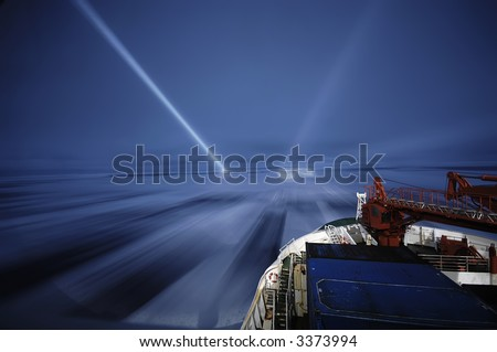 Icebreaking in Antarctica during night with a research vessel. By bright light beams the ship is in search of dangerous icebergs. The long exposure picture was taken during a 3-month expedition. - stock photo