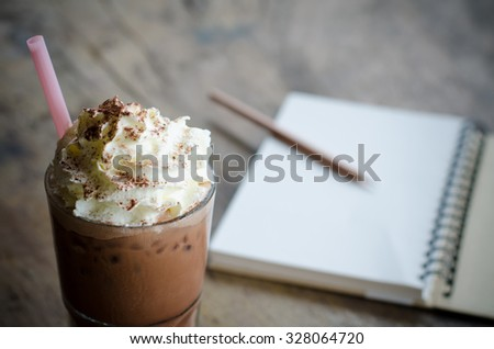 iced cocoa in a glass and note book - stock photo