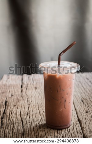 iced cocoa in takeaway cup on wooden table background