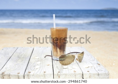 Iced coffee and glasses on a wooden table on the beach.  - stock photo