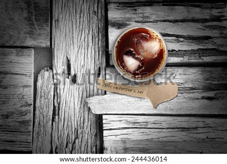 Iced coffee and torn paper in heart shape on wood floor, background for valentine's day. - stock photo