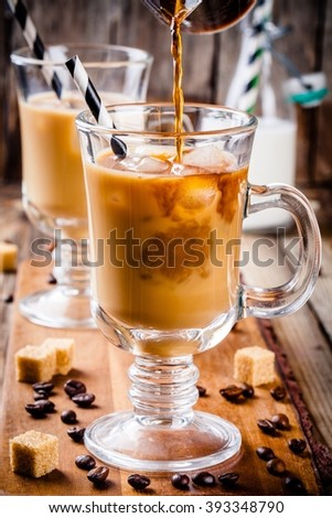 Iced coffee in mugs on wooden table