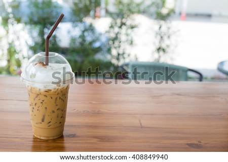 Iced coffee in plastic glass on wooden table. Selective focus. - stock photo