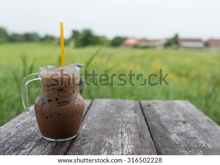 Iced Coffee Mocha on the wood table in rice fields thailand - stock photo