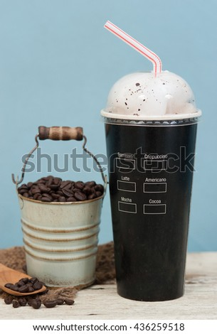 Iced coffee with coffee beans on wood vintage background,Selective focus on paper cup - stock photo