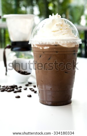 Iced coffee with cream in take away cup on white background .Ice coffee with whipped cream and coffee beans  on a white table