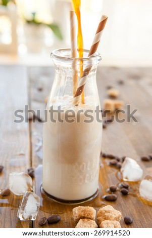 Iced coffee with milk in vintage milk bottle - stock photo