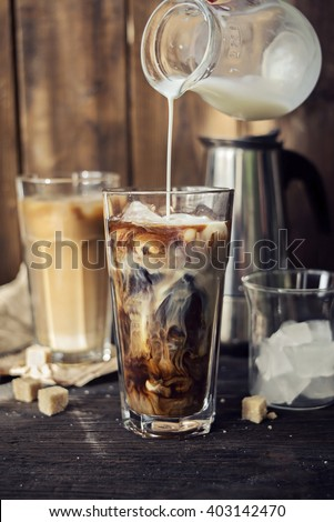 Iced coffee with pouring milk in two glasses  - stock photo