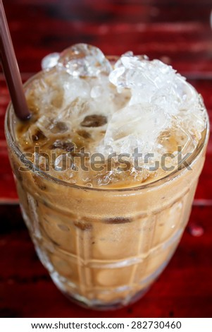 iced coffee with straw in glass cup.