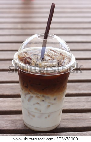 Iced coffee with straw in plastic cup on table