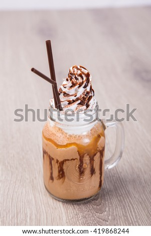 Iced coffee with whipped cream on wooden table - stock photo