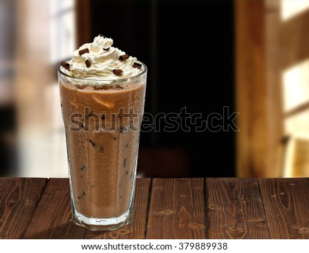 Iced coffee with whipped cream on wooden table at cafe - stock photo