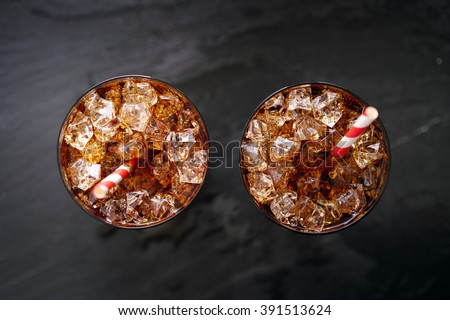 iced cola soda pop with straw in flay lay composition - stock photo