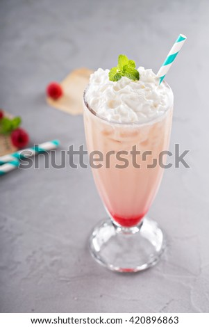 Iced milkshake with raspberry syrup topped with whipped cream