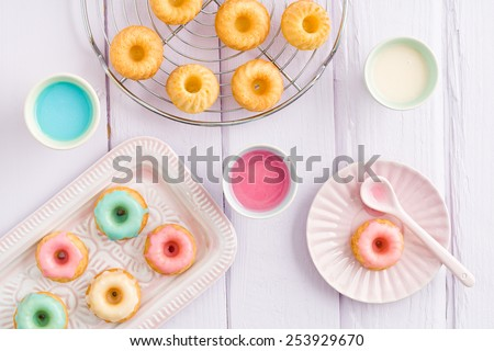 Iced mini bundt cakes with icing, a tray and a spoon - stock photo