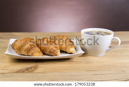 Iced mocha coffee with croissants on wooden table with purple background