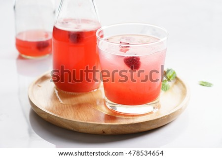 iced red raspberry drinks in glass and bottle on white marble table