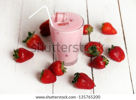 Iced strawberry pink cocktail in a glass and strawberries