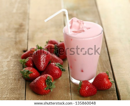 Iced strawberry pink cocktail in a glass and strawberries - stock photo