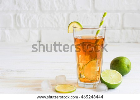 Iced tea in a glass with a slice of lime. White wooden plank background