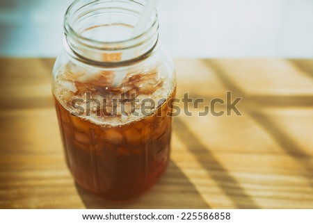 Iced tea in a jar with ice and a straw on a wooden board against a brightly lit background.  - stock photo