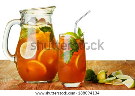 Iced tea in the pitcher and the glass.  Jug of cold iced drink with lemon and mint on wooden table over plain white background. - stock photo