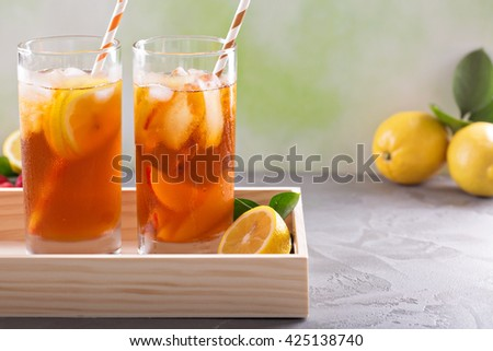 Iced tea variety in tall glasses on green background - stock photo