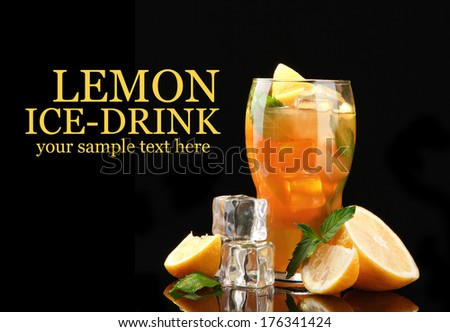 Iced tea with lemon and mint on black background  - stock photo