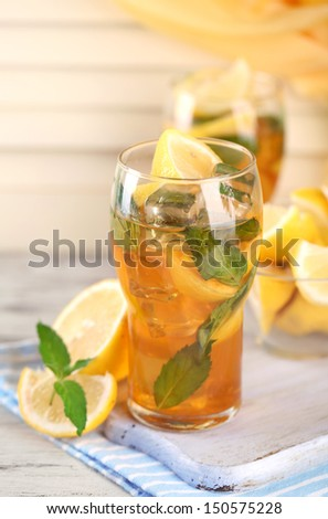 Iced tea with lemon and mint on wooden table
