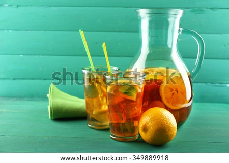 Iced tea with lemon on  color wooden background - stock photo
