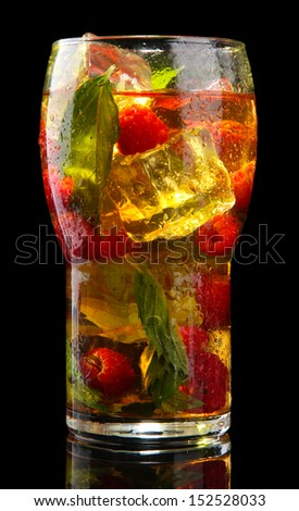 Iced tea with raspberries and mint on black background