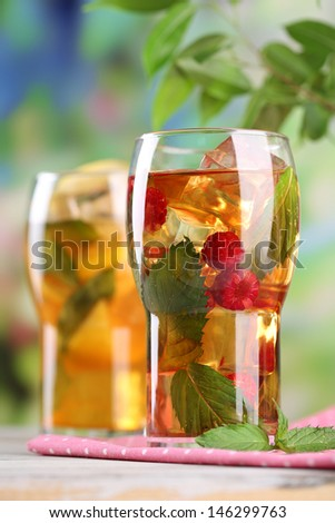 Iced tea with raspberries, lemon and mint on wooden table, outdoors