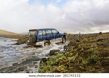 ICELAND - 29 August 2012 Big blue four by four off road car crossing a river stream on the rouad to Askja in the Icelandic Tundra