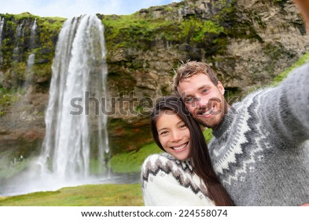 Iceland couple selfie wearing Icelandic sweaters by Seljalandsfoss waterfall on Ring Road in beautiful nature landscape on Iceland. Woman and man model in typical Icelandic sweater. Multiracial couple - stock photo