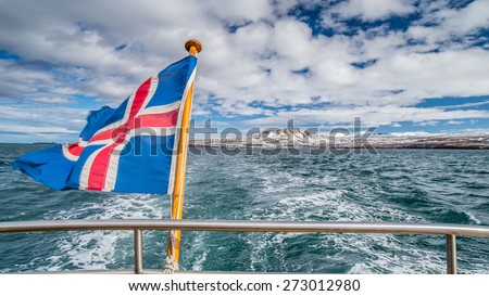 Iceland flag on boat while leaving shore - stock photo