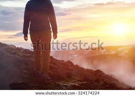 Iceland geothermal lava fields with steam from hot ground tourist walking on dangerous unstable cliff - stock photo