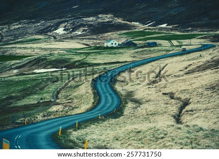 Iceland nature landscape road  with clouds and amply field village and lake river   - stock photo