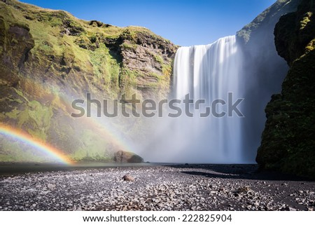 Iceland, Skogafoss with double rainbow, no people, blue sky - stock photo