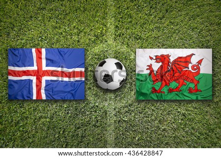 Iceland vs. Wales flags on green soccer field