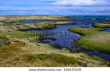 Icelandic Coastline in May:  Lava fields covered with moss and grass meet the Atlantic Ocean on the south coast of Iceland between Reykjavik and Keflavik. - stock photo
