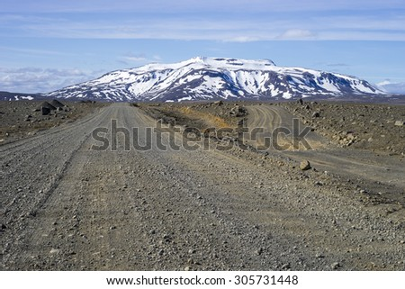 Icelandic dirt track (550) in south west highlands with snow covered Ok shield volcano in the backgroud - stock photo