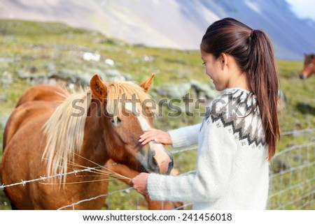 Icelandic horses - woman petting horse on Iceland. Girl in sweater going horseback riding smiling happy with horse in beautiful nature on Iceland. - stock photo