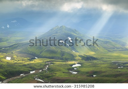 Icelandic landscape - sun shining through the clouds on a mountain at the Laugavegur hiking trail near Alftavatn on Iceland.