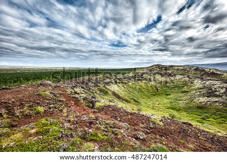 Icelandic landscape with moss, grass and beautiful cloudy sky