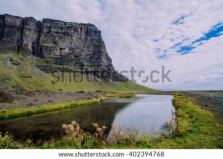 Icelandic landscape with rock and lake - stock photo