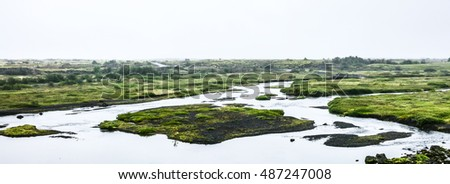 Icelandic landscape with view on river with island