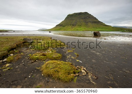 Icelandic landscapes with dominant hill and cloudy sky - stock photo