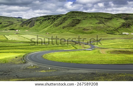 Icelandic mountain landscapes with curved asphalt road - stock photo