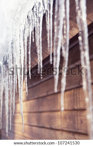 Icicle on wooden roof - stock photo