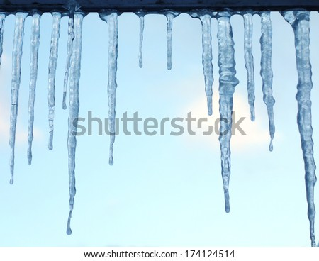 Icicles against blue sky - stock photo